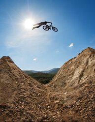 Silhouette of man with bicycle jumping on mountain against sky - CAVF06161
