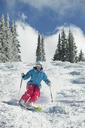 Happy woman skiing downhill on mountain - CAVF06176