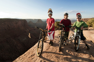 Portrait of mountain bikers with bicycles standing on cliff - CAVF06188