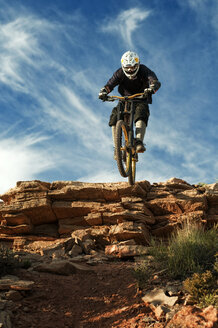Mountain biker jumping from cliff against sky - CAVF06197