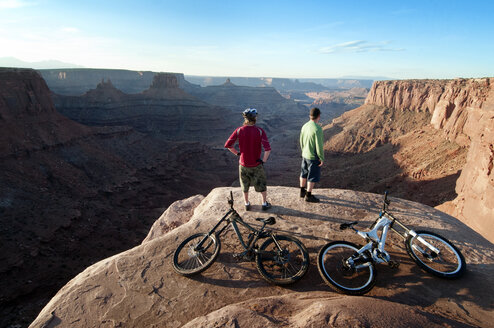 Rear view of mountain bikers standing on cliff - CAVF06206