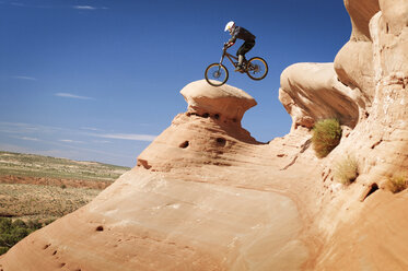 Side view of cyclist jumping from mountain against blue sky - CAVF06209