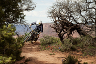 Cyclist riding bicycle on dirt road in forest - CAVF06215