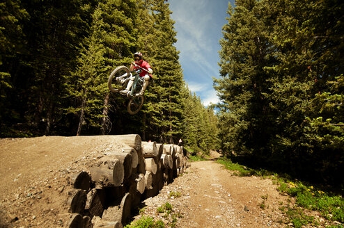 Cyclist performing stunt on logs in forest - CAVF06224