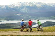 Rear view of cyclists on field against mountains - CAVF06230