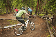 Cyclists cycling on dirt road in forest - CAVF06233