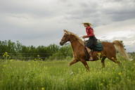 Side view of woman riding on horse against clouds sky - CAVF06278