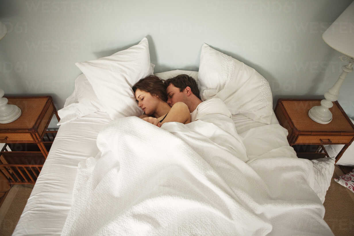 High angle view of couple sleeping on bed at home - CAVF06332 - Cavan Images/Westend61