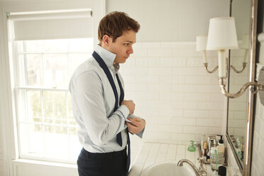Side view of man getting dressed while standing at bathroom sink - CAVF06335