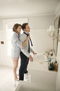 Woman assisting man in tying necktie while standing at bathroom sink - CAVF06338