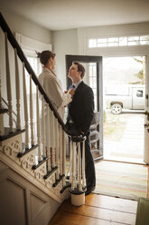 Woman adjusting man's tie while standing on staircase at home - CAVF06344