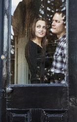 Happy couple looking away while standing by window at home - CAVF06350