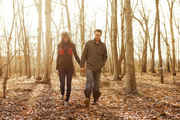 Couple holding hands while walking in forest - CAVF06359