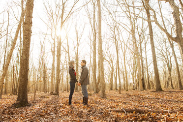 Side view of couple holding hands while standing in forest - CAVF06362