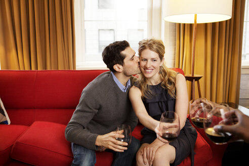 Happy man kissing girlfriend holding wineglass - CAVF06374