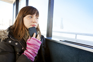 Woman with mobile phone looking away while traveling in ferry - CAVF06482