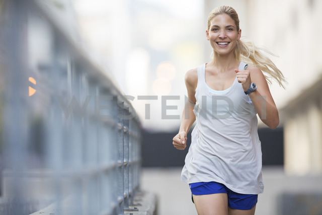Woman running through city streets - CAIF15173