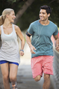 Couple running through city streets together - CAIF15179