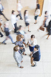 High angle view of Business people standing in office, talking and smiling - CAIF15266