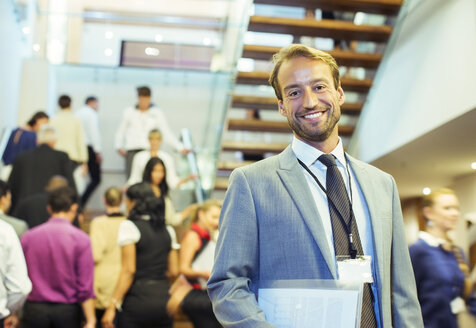 Portrait of smiling businessman holding file, standing in crowded lobby of conference center - CAIF15269