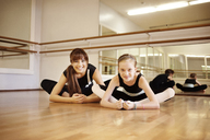 Portrait of teacher and student practicing Cobbler pose in dance studio - CAVF06590