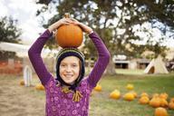 Portrait of girl carrying pumpkin on head in farm - CAVF06770