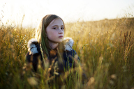 Thoughtful girl looking away while standing on field - CAVF06788