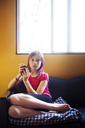 Portrait of girl using mobile phone while sitting on sofa at home - CAVF06812