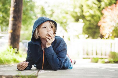 Boy holding chalk while lying on footpath - CAVF06845