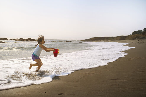 Side view of girl carrying bucket while running on shore at beach - CAVF06893