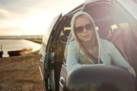 Woman looking through window while sitting in car - CAVF06926
