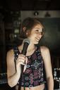 Girl looking away while singing in recording studio - CAVF06938