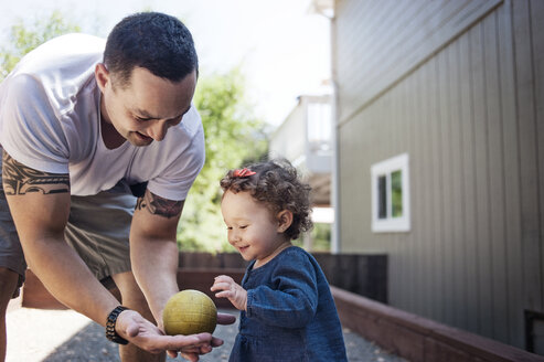 Father giving ball to baby while standing in backyard - CAVF06953