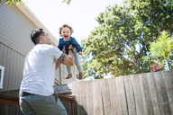 Low angle view of father lifting daughter while standing in backyard - CAVF06956