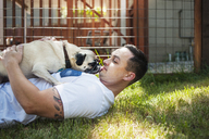 Man playing with pug on grassy field in backyard - CAVF06962