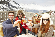 Friends celebrating with drinks in the snow - CAIF15299