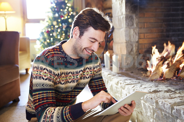Man using digital tablet in front of fireplace - CAIF15308