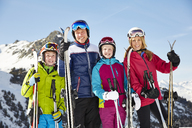 Smiling family holding ski poles on mountain - CAIF15374