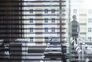 Young businessman standing in conference room looking out of window - CAIF15425