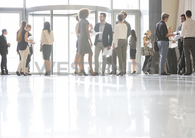 Group of business people standing and talking in office - CAIF15428
