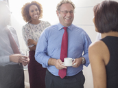 Businessman talking to colleagues in office and holding coffee cup - CAIF15437