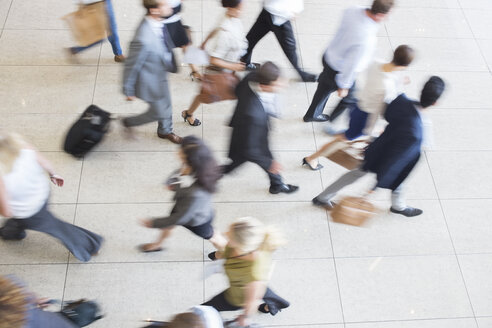 High angle view of business people walking in office on tiled floor - CAIF15464