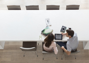 Elevated view of couple using tablet pc in dining room - CAIF15515