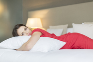 Portrait of beautiful woman wearing red dress lying on bed and hugging pillow - CAIF15524