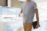 Man carrying coffee cup and digital tablet walking through modern kitchen - CAIF15530