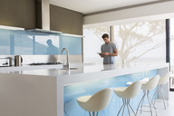 Man using digital tablet in modern kitchen - CAIF15536