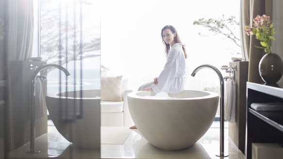 Portrait of smiling woman wearing white bathrobe, sitting on edge of bathtub in bathroom - CAIF15539