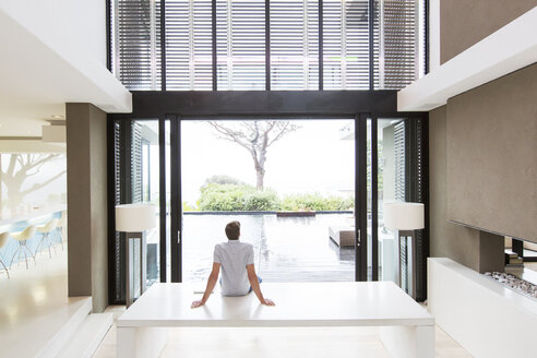 Rear view of man sitting on table and looking at swimming pool through open patio door - CAIF15545