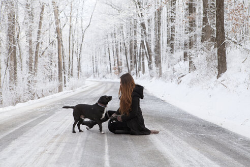 Side view of woman with dog on road during winter - CAVF06977