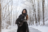 Woman carrying dog while standing on road during winter - CAVF06980